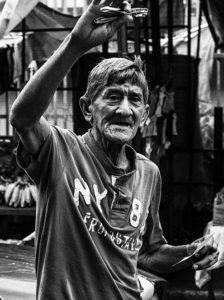 stary człowiek z podniesioną ręką