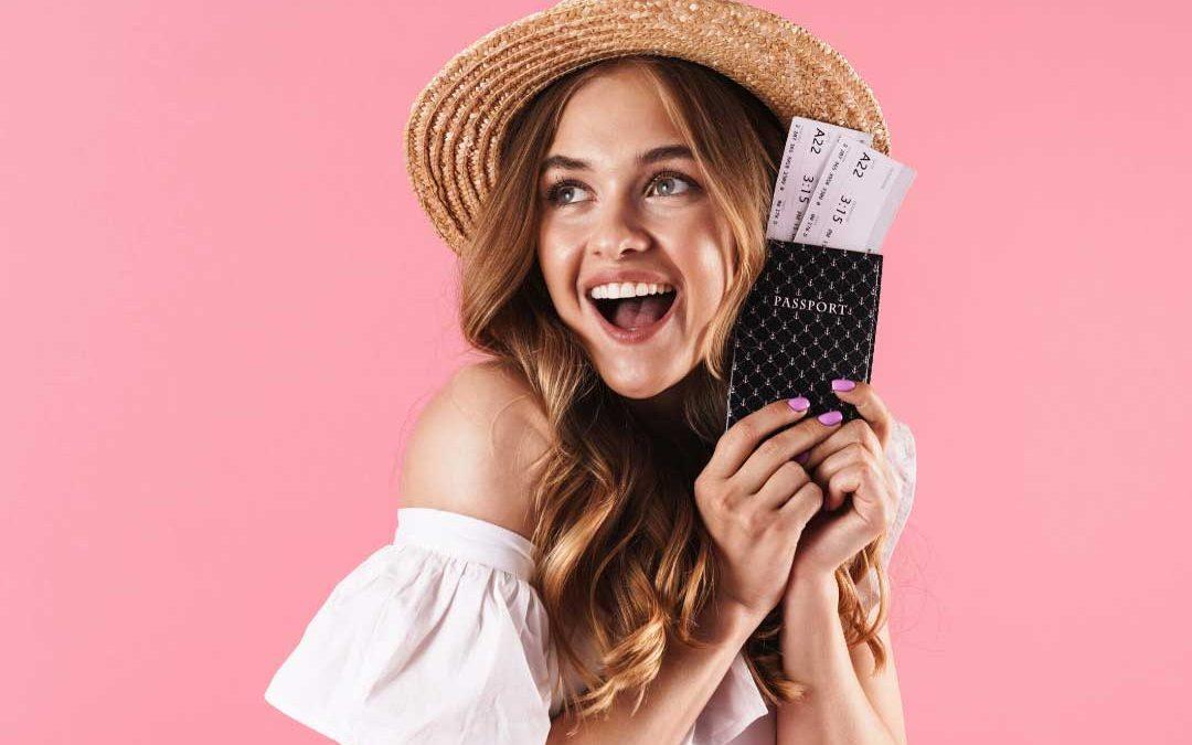 uśmiechnięta dziewczyna w kapeluszutrzyma paszport z biletami lotniczymi