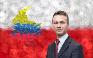 mężczyzna w garniturze w tle flaga polski i kolumbii