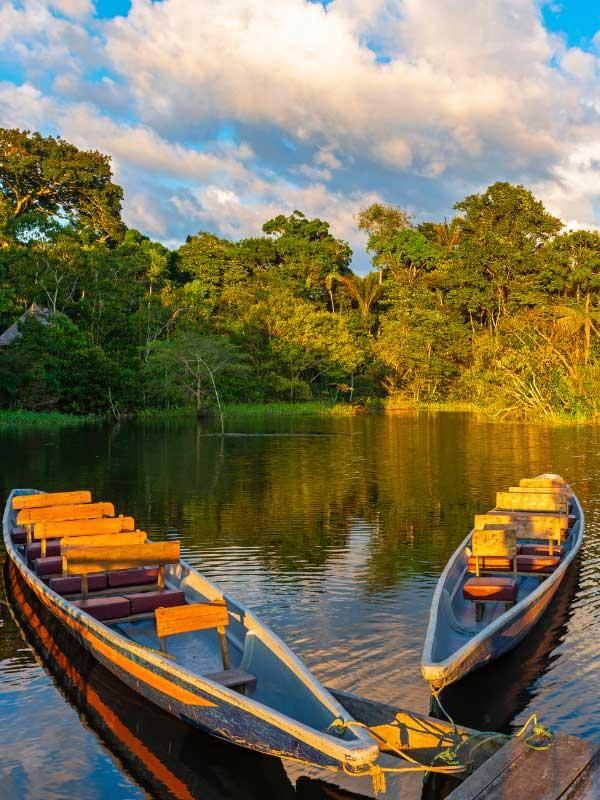 dwie łódki na rzece przy zachodzie słońca
