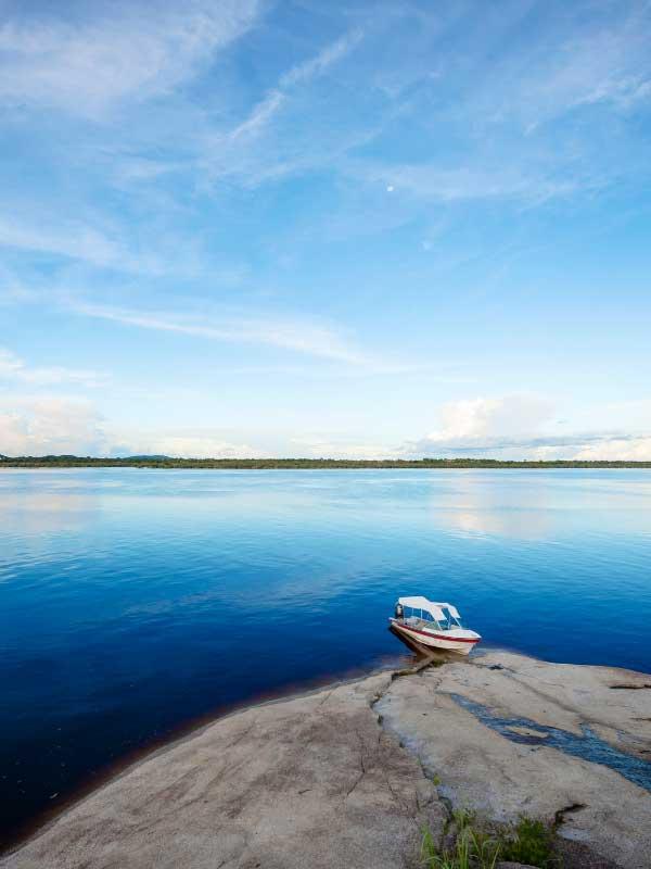 łódka zacumowana przy brzegu rozległej rzeki