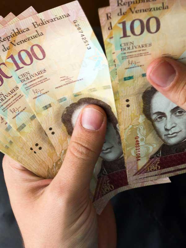 Banknoty boliwara wenezuelskiego w dłoniach