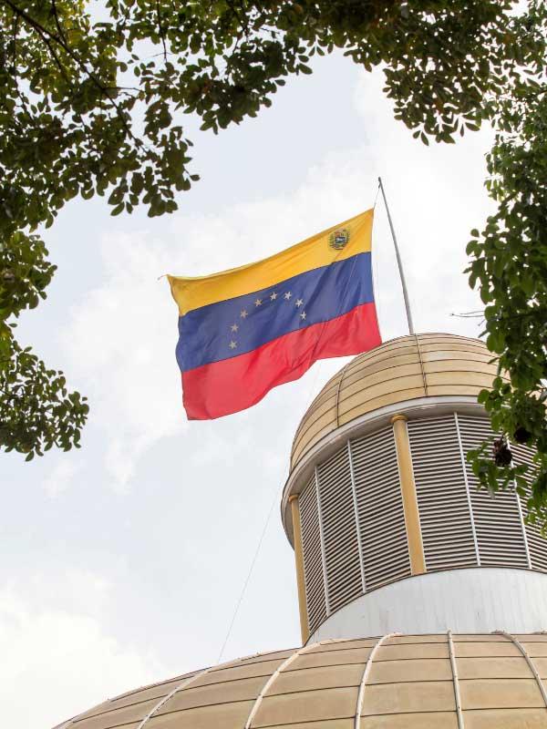 Flaga Wenezueli powiejwająca na kolule budynku