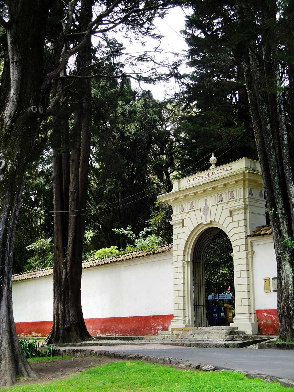Biały mur i duże wejście zatopione w drzewach