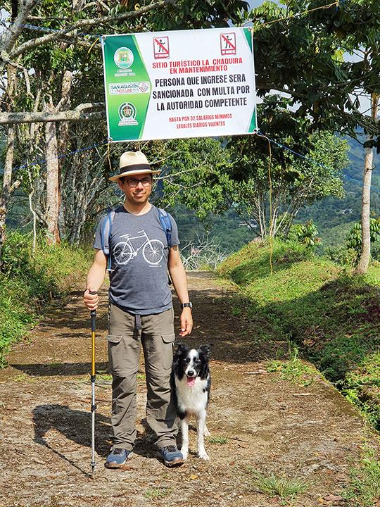mężczyzna z psem stoi na ścieżce a za nim zakaz przejścia