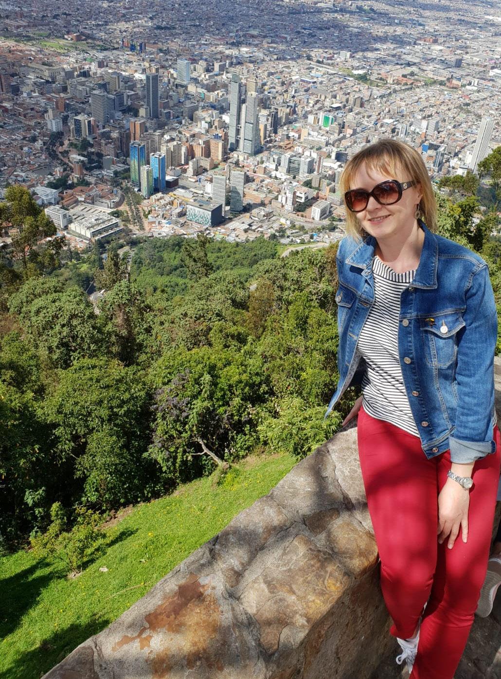 Uśmiechnięta kobieta z panoramą miasta za nią