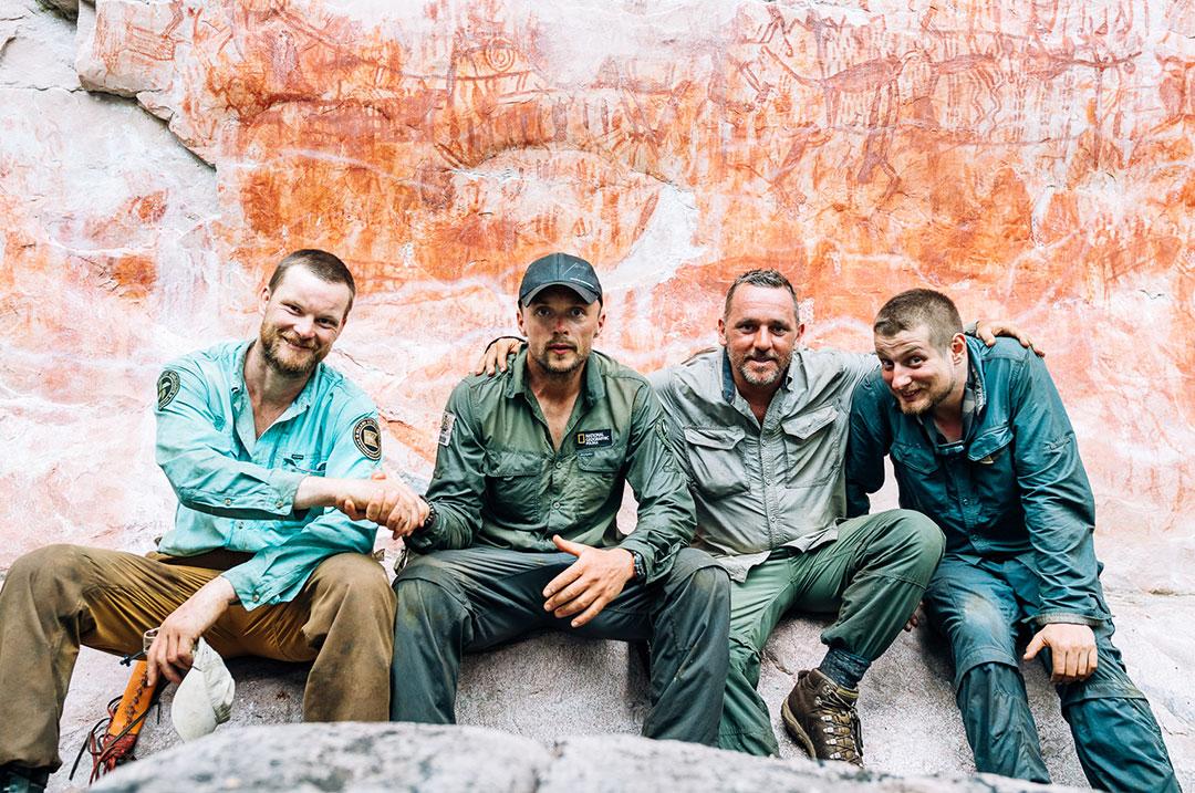 czterech mężczyzn siedzi przed ścianą z malowidłami naskalnymymi
