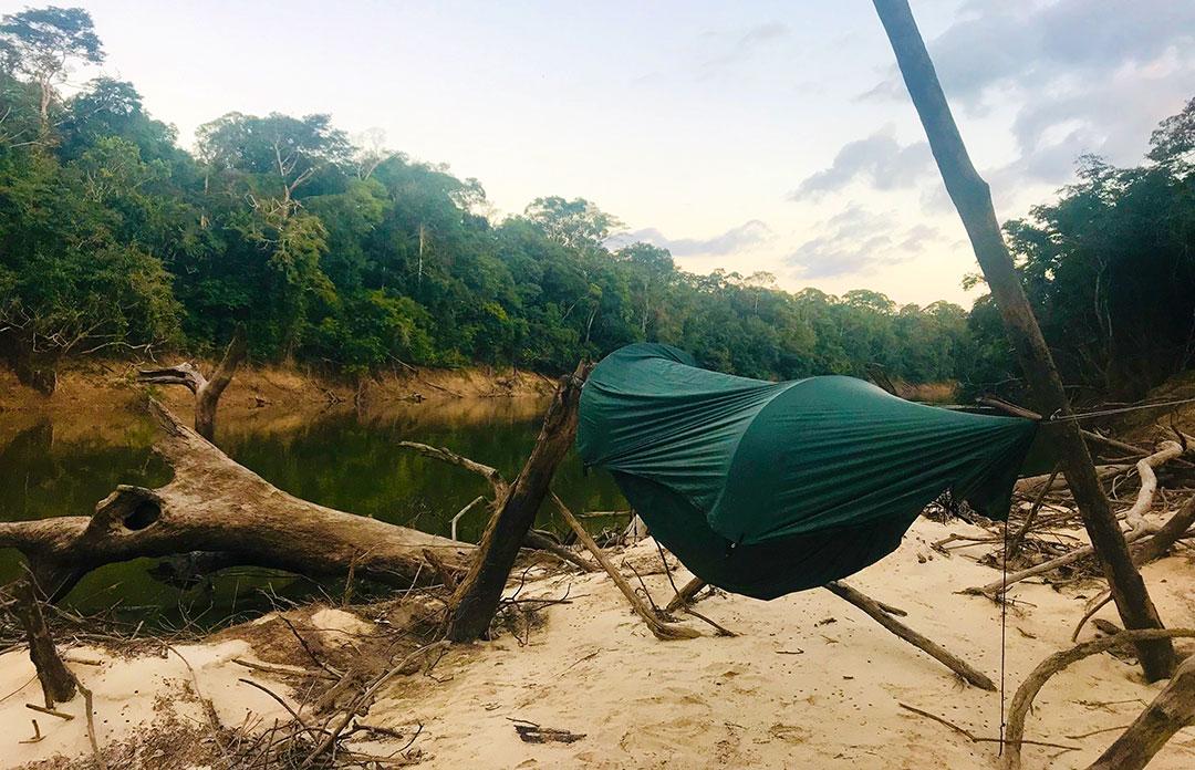 Hamak-namiot zawieszony na palach na plaży przy brzegu rzeki